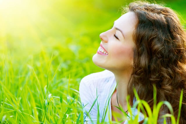 Image of Woman Sitting on the Field with Sun Shining -Texas - Freedom Health Centers