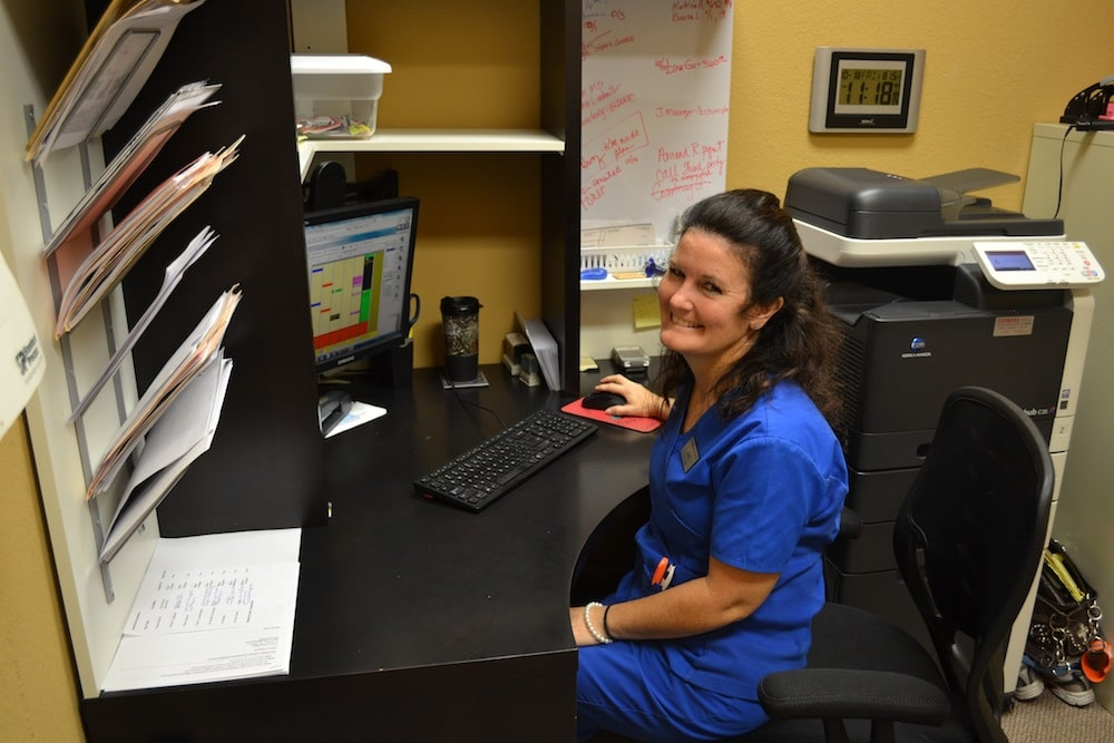 Image of Chris Newman, Office Manager, from the Freedom Health Centers of McKinney Texas Sitting In Front of Monitor Smiling