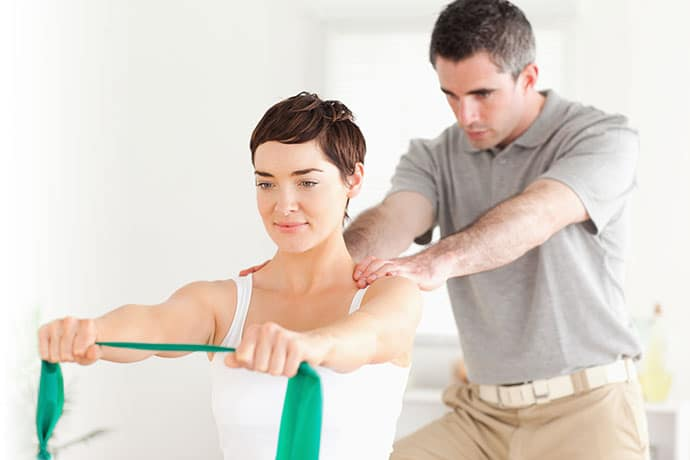 Image of Woman Doing Physical Therapy & Rehabilitation with the Help of Male Chiropractor - Freedom Health Centers
